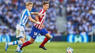 Odegaard y Marcos Llorente pelean por un balón durante el partido.