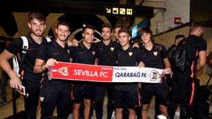 Varios jugadores posan con la bufanda del partido, en el aeropuerto.