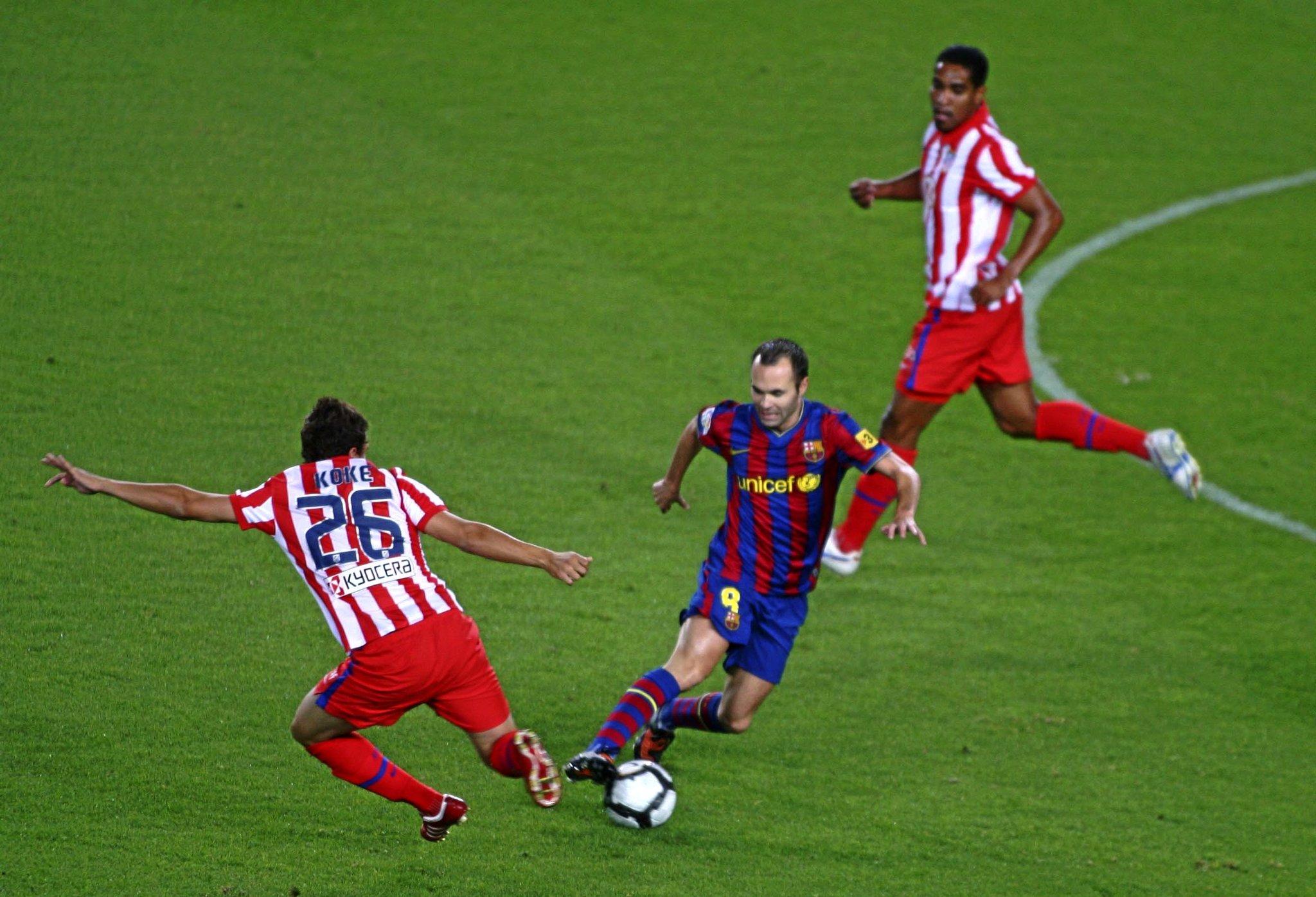 Koke, en su debut, disputando un balón con Iniesta