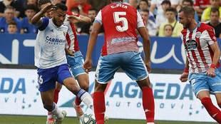 Luis Suárez conduce el balón ante la presencia de tres jugadores del...