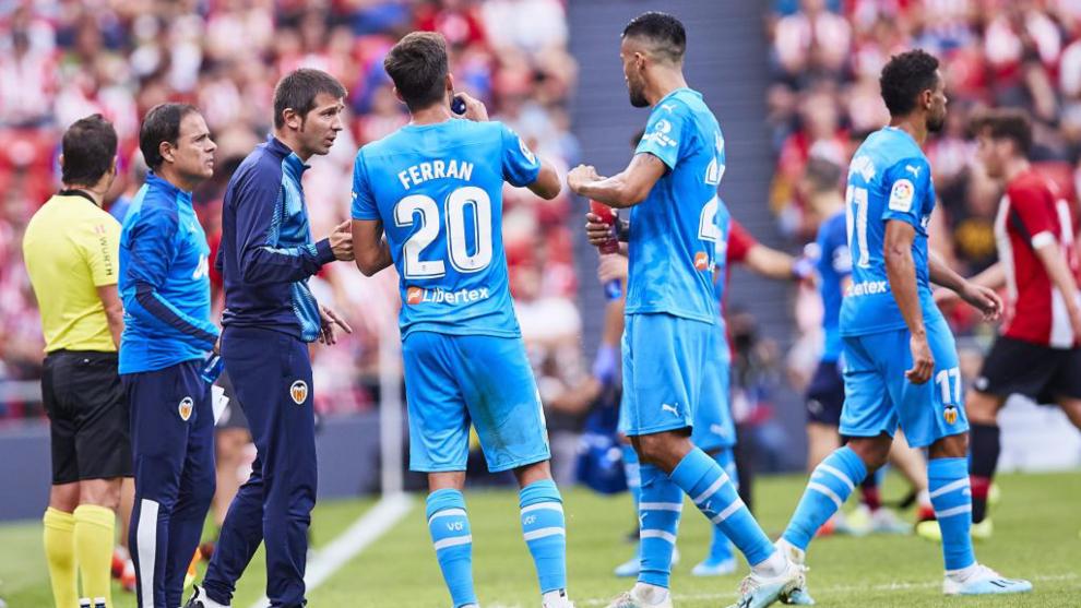 Los jugadores hablan con Celades durante el partido.