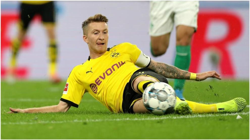 Marco Reus trata de rebañar un balón desde el suelo.