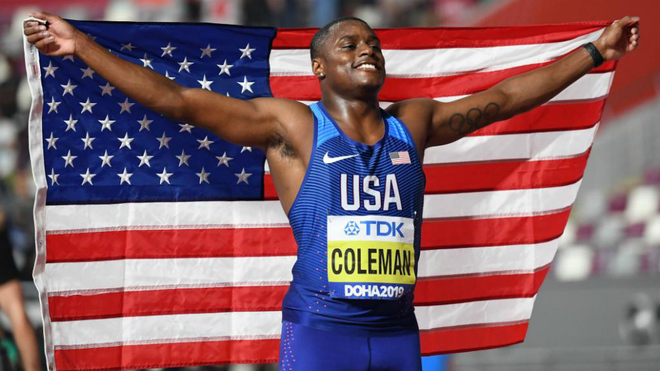 Christian Coleman posa con la bandera de Estados Unidos tras ganar la...