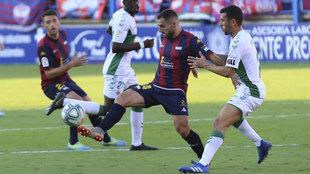 Nono y Pérez Milla pugna por un balón durante el Extremadura-Elche.