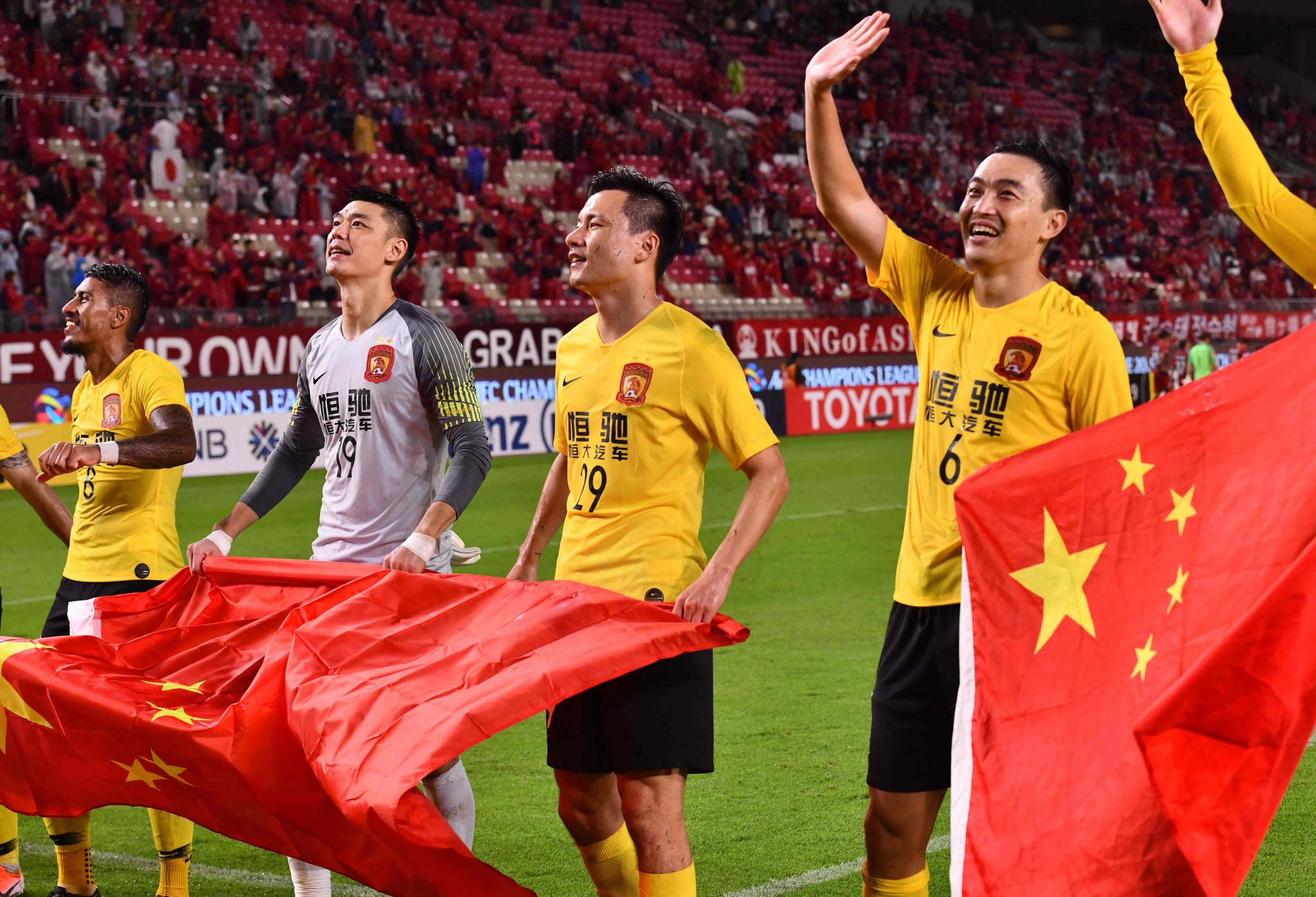 Guangzhous defender Feng Xiaoting (R), forward Gao Lin (2nd R), goalkeeper Zeng Cheng (2nd L) and midfielder Paulinho (L) celebrate their qualifying for the semi-finals with supporters after the AFC Champions League quarter-finals second leg football match between Kashima Antlers of Japan and Guangzhou <HIT>Evergrande</HIT> of China at the Kashima Stadium in Kashima, Ibaraki prefecture on September 18, 2019. (Photo by TOSHIFUMI KITAMURA / AFP)