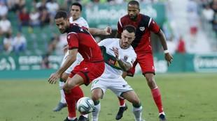 Mario Suárez y Josan disputan un balón en el Martínez Valero