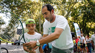 Costa enseña a un niño a coger la raqueta