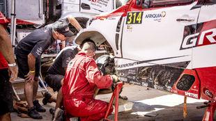 Mecánicos de Toyota, arreglando el Hilux 314 de Alonso ayer en el...