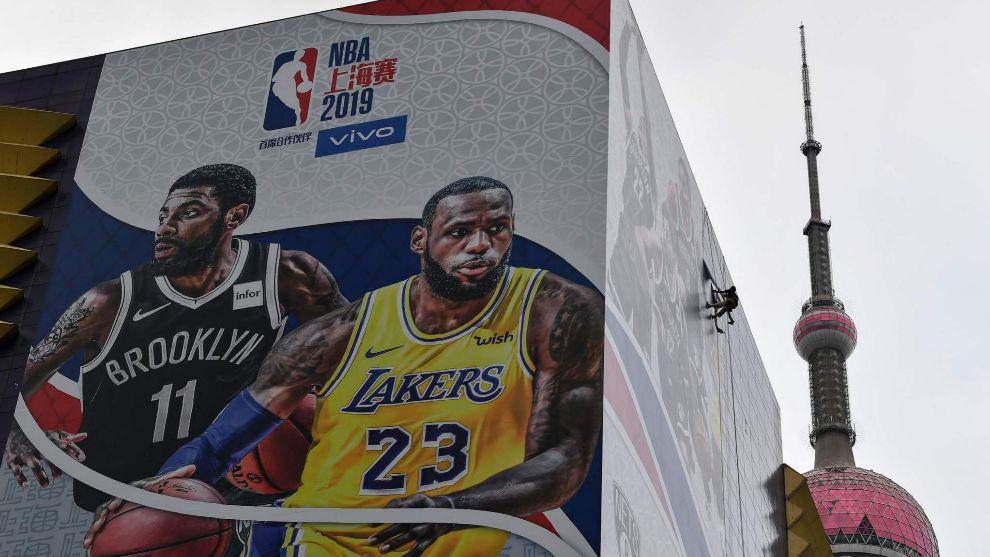 Operarios chinos retiran el cartel del anuncio de partido entre Lakers...