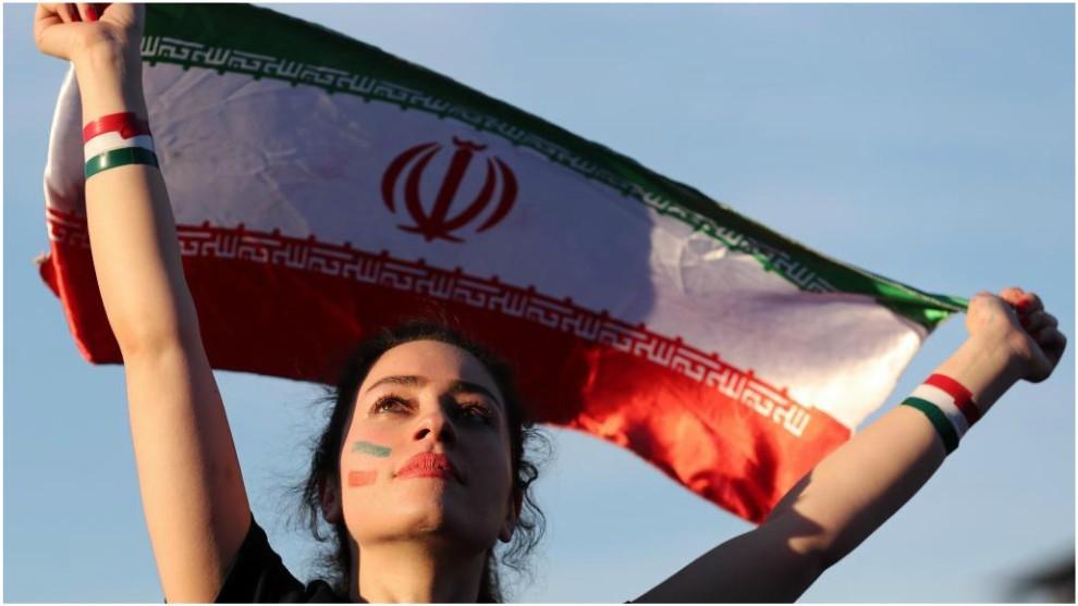 Una aficionada iraní levanta una bandera en señal de libertad.