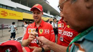 Vettel firma un autógrafo a un aficionado japonés en Suzuka.