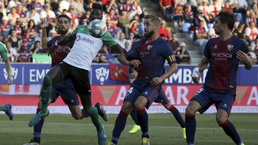 Nuha intenta controlar el balón entre varios jugadores del Huesca