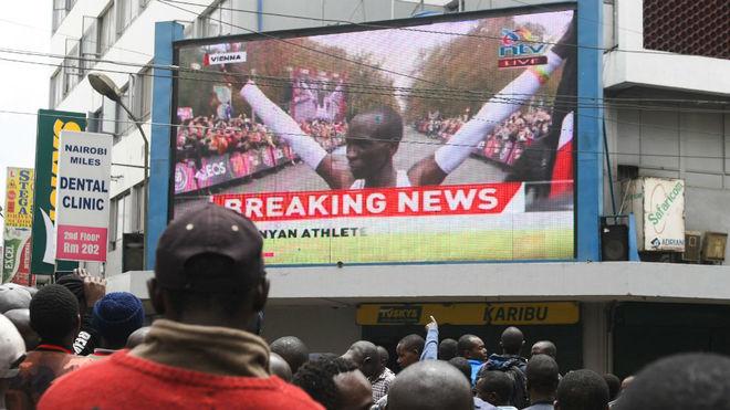Cientos de personas presencian la hazaña de Kipchoge en una pantalla...