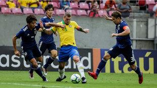 Lyanco es perseguido por tres jugadores japoneses durante el partido...