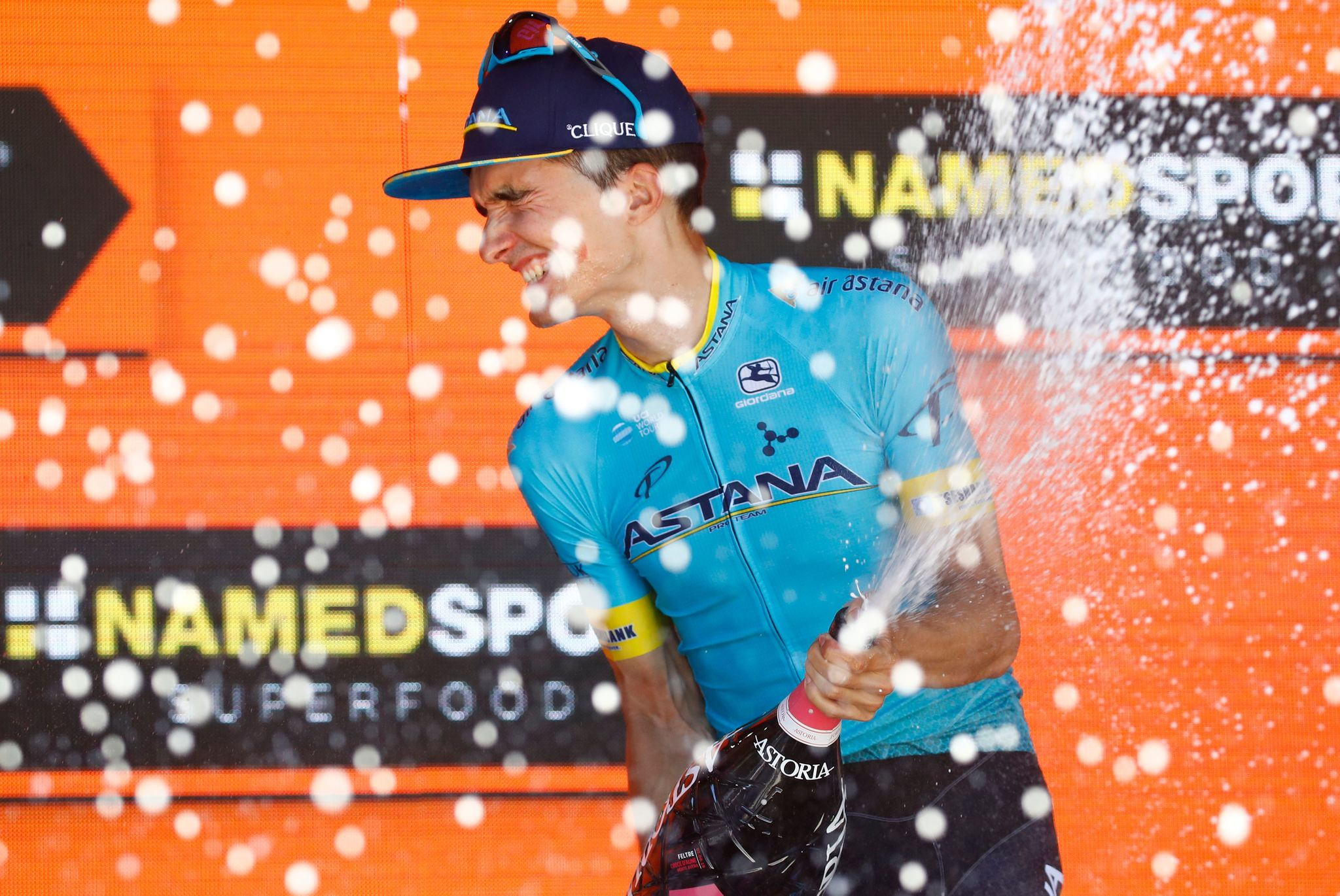 Team Astana rider Spains <HIT>Pello</HIT><HIT>Bilbao</HIT> sprays champagne as he celebrates on the podium after winning stage twenty of the 102nd Giro dItalia - Tour of Italy - cycle race, 194kms from Feltre to Croce DAune-Monte Avena on June 1, 2019. (Photo by Luk BENIES / AFP)