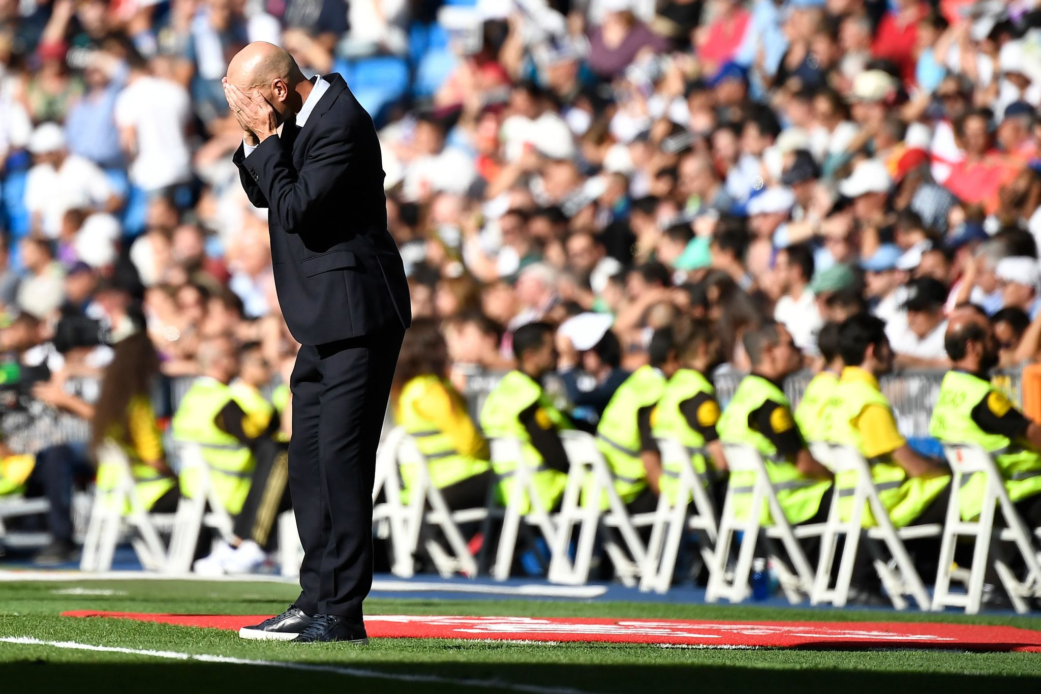 Real Madrids French coach Zinedine <HIT>Zidane</HIT> covers his face during the Spanish league football match between Real Madrid CF and Granada FC at the Santiago Bernabeu stadium in Madrid on October 5, 2019. (Photo by PIERRE-PHILIPPE MARCOU / AFP)