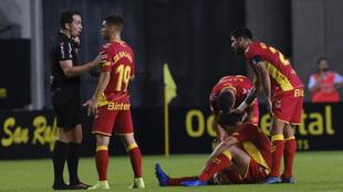 El colegiado Ais Reig y jugadores de Las Palmas en el encuentro de...