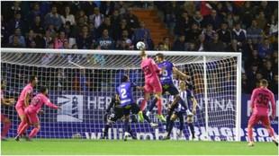 Mikel Villanueva salta para tocar el balón junto al local Óscar...
