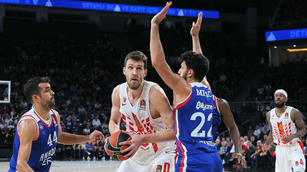 Ognjen Kuzmic trata de superar la defensa de Vasilije Micic y...