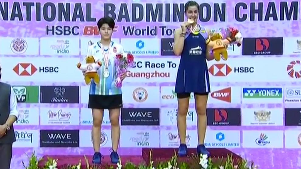 Carolina Marín muerde su medalla en el podio, junto a la tailandesa...