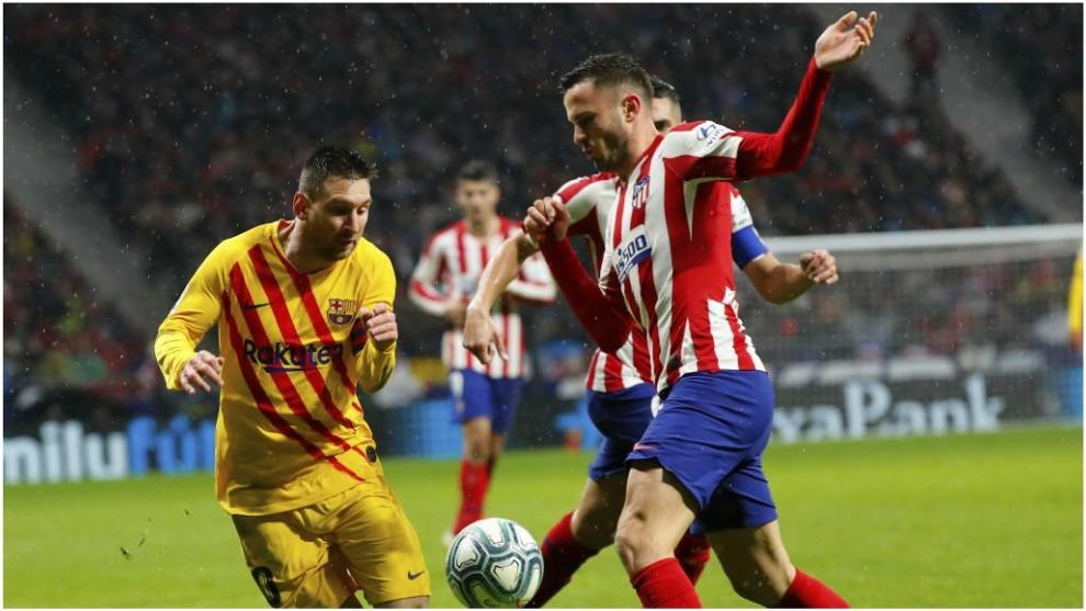 Saúl disputa un balón con Messi