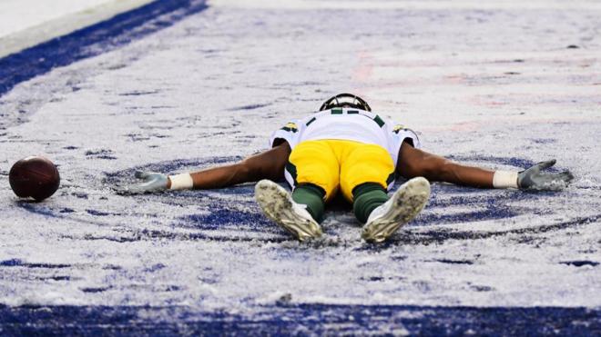Aaron Jones de los Green Bay Packers hace un angel en la nieve del...