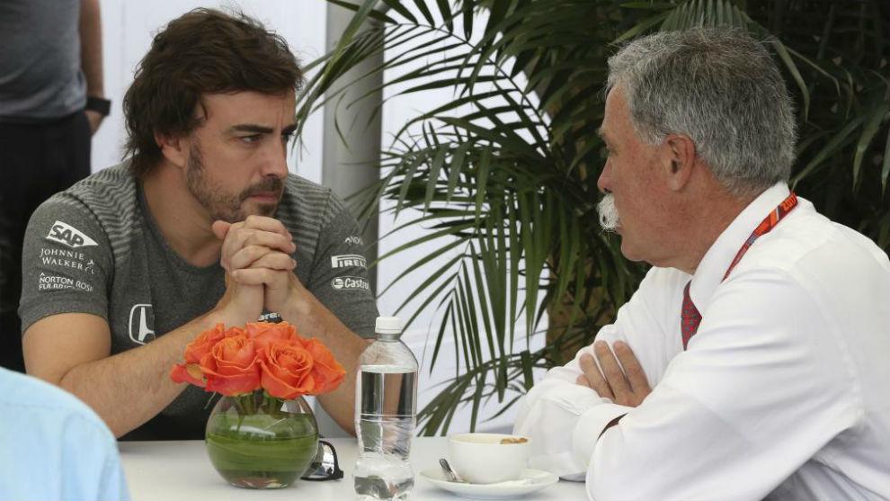 Alonso y Carey, charlando durante un gran premio de F1.
