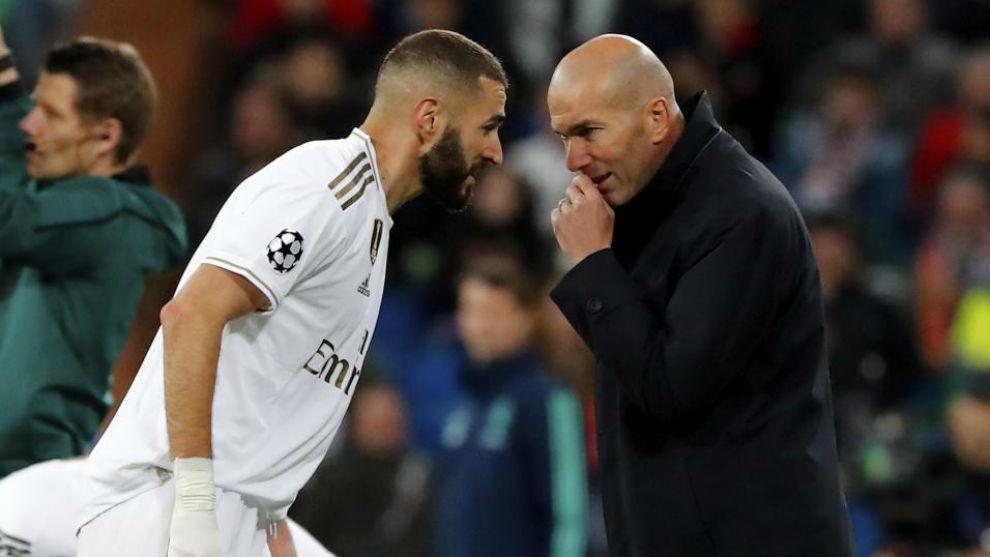 Benzema y Zidane hablan durante un partido.