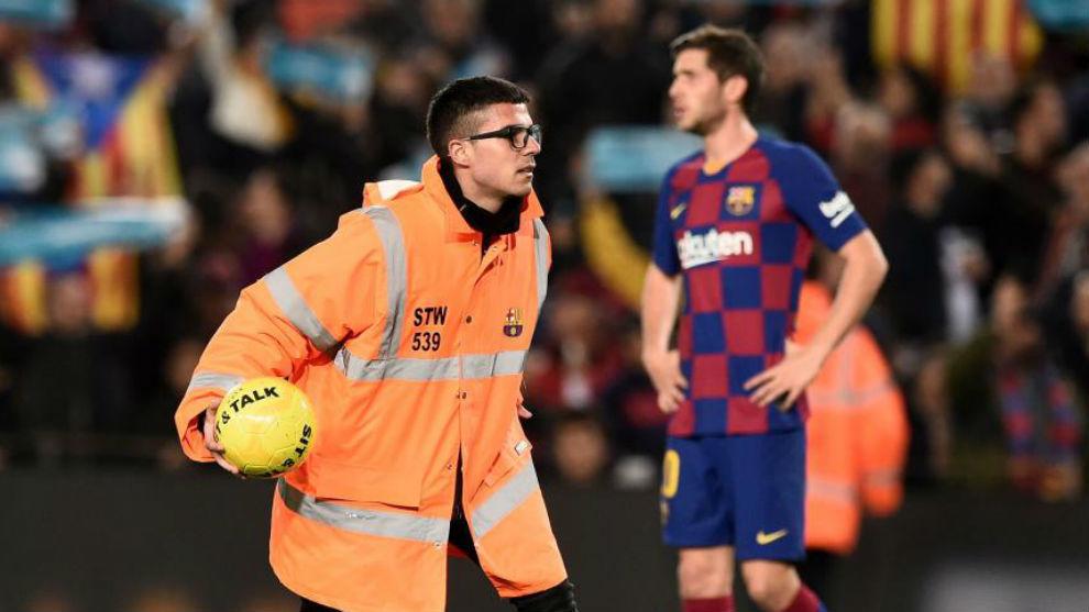Un miembro de seguridad retira un balón ante Sergi Roberto