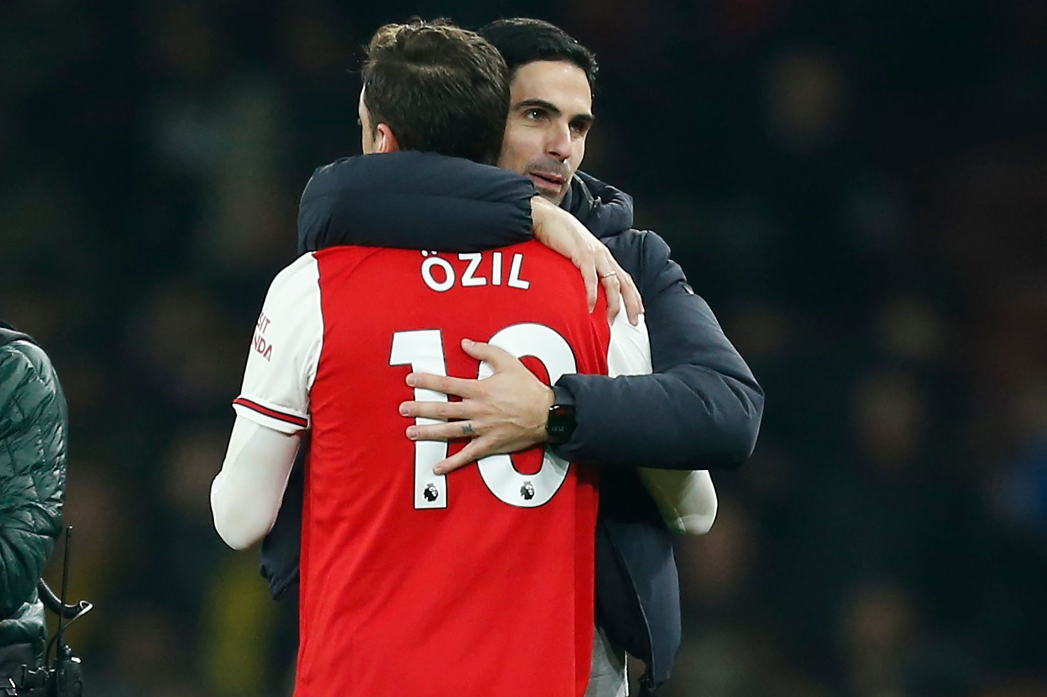 Arsenals Spanish head coach Mikel Arteta (R) embraces Arsenals German midfielder Mesut <HIT>Ozil</HIT> (L) on the pitch after the English Premier League football match between Arsenal and Manchester United at the Emirates Stadium in London on January 1, 2020. - Arsenal won the game 2-0. (Photo by Ian KINGTON / IKIMAGES / AFP) / RESTRICTED TO EDITORIAL USE. No use with unauthorized audio, video, data, fixture lists, club/league logos or live services. Online in-match use limited to 45 images, no video emulation. No use in betting, games or single club/league/player publications
