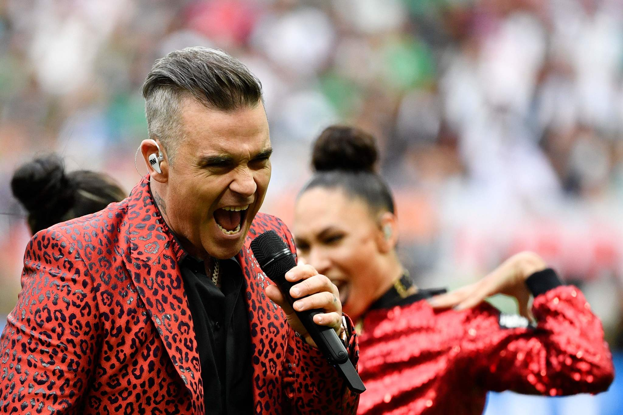 English singer <HIT>Robbie</HIT><HIT>Williams</HIT> performs during the opening ceremony before the Russia 2018 World Cup Group A football match between Russia and Saudi Arabia at the Luzhniki Stadium in Moscow on June 14, 2018. / AFP PHOTO / Alexander NEMENOV / RESTRICTED TO EDITORIAL USE - NO MOBILE PUSH ALERTS/DOWNLOADS