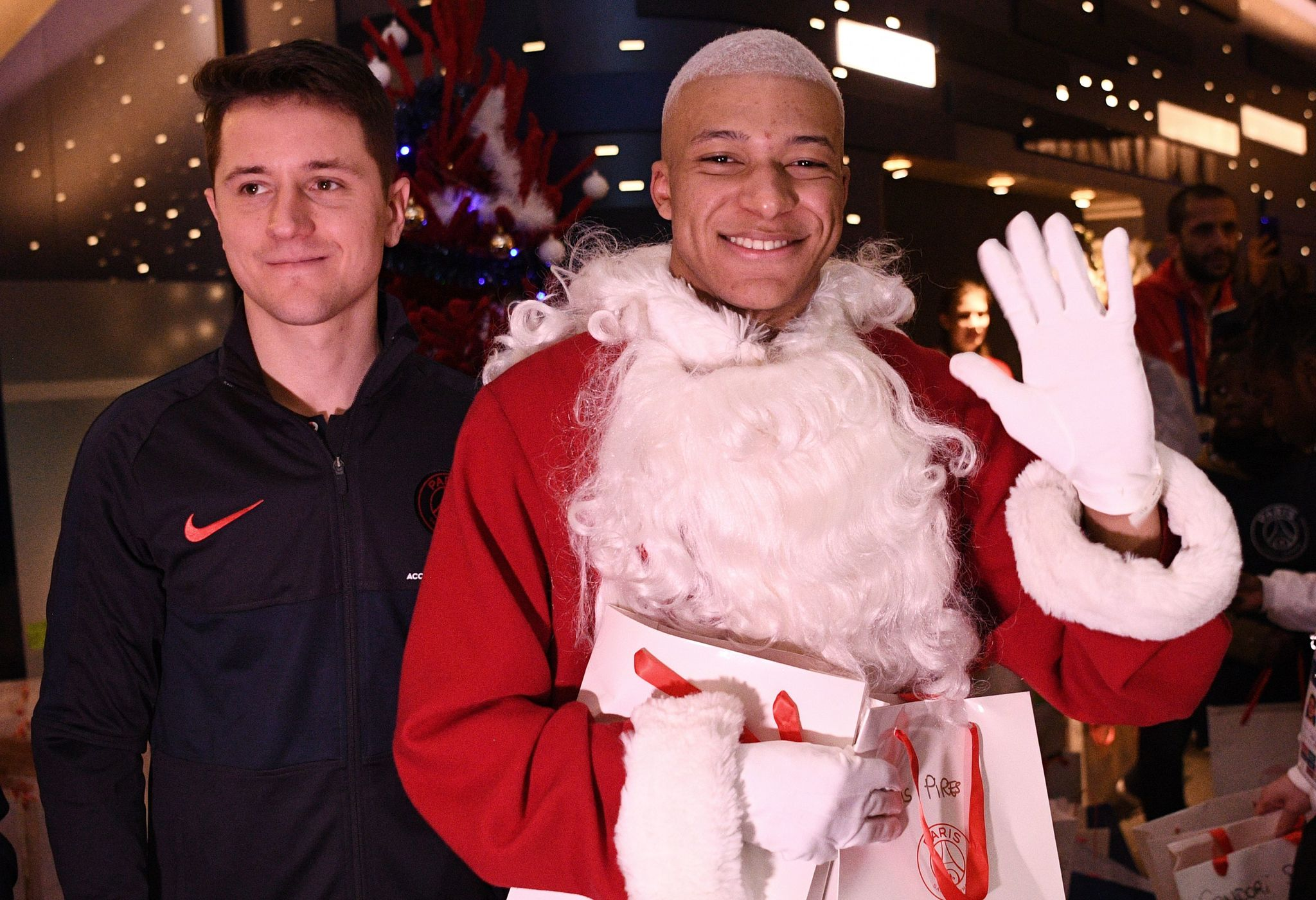 TOPSHOT - Paris Saint-Germains Spanish midfielder Ander Herrera (L) and Paris Saint-Germains French forward Kylian MBappe dressed as Santa Claus pose for a picture as they give gifts to children from the Paris Saint-Germains foundation after the French Ligue 1 football match between Paris Saint-Germain (<HIT>PSG</HIT>) and Amiens SC (ASC) at the Parc des Princes stadium in Paris on December 21, 2019. (Photo by FRANCK FIFE / AFP)