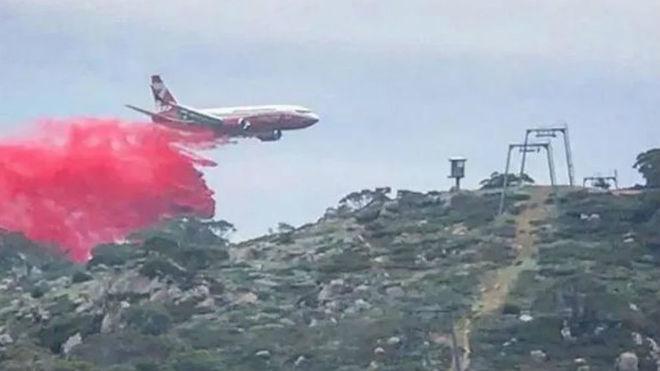 Un avión descarga líquido retardador del fuego sobre Perisher Valley