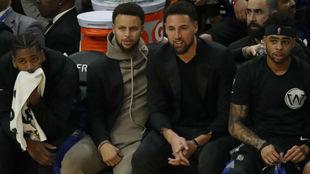 Klay Thompson viendo un partido de los Warriors junto a Stephen Curry
