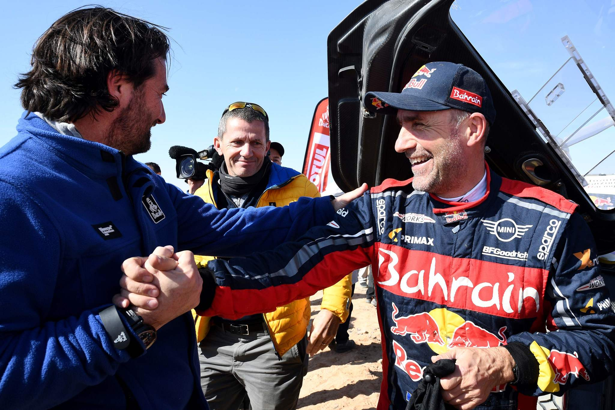 Auto category third-placed JCW X-RAID Mini Team Frances Stephane <HIT>Peterhansel</HIT> (R) shakes hands of The Dakar Rally director David Castera (L) next to Managing director of Amaury Sport Organisation (ASO) Yann Le Moenner (C) on the finish area in Qiddiya at the end of the stage 12 of the Dakar 2020 between Haradh and Qiddiya, Saudi Arabia, on January 17, 2020. (Photo by FRANCK FIFE / AFP)