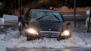 Un coche transita una calle inundada de Ibiza