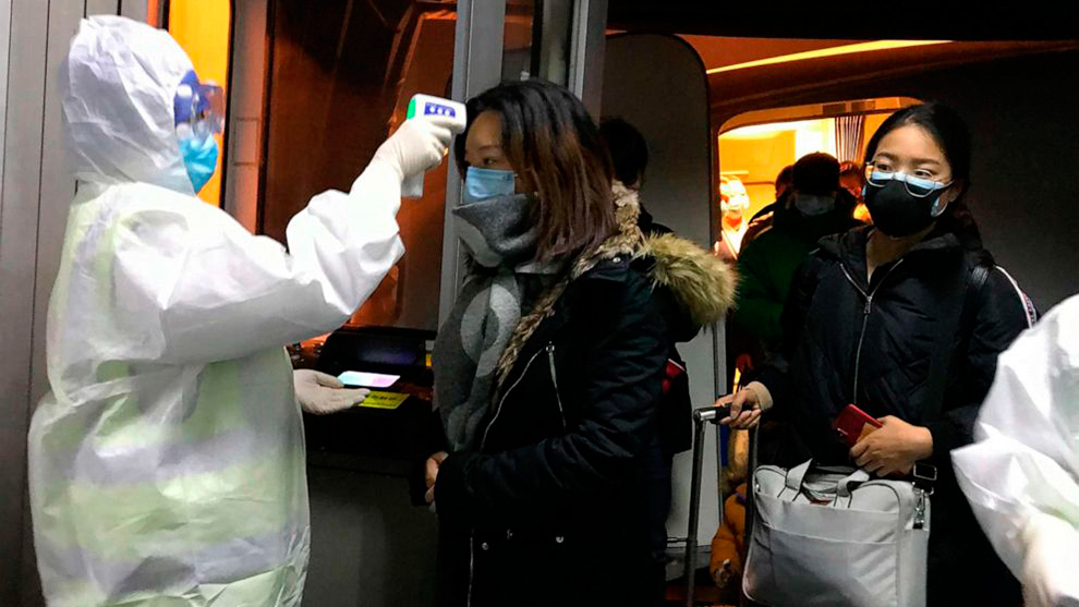 Oficiales de salud analizan a los pasajeros en el aeropuerto de...