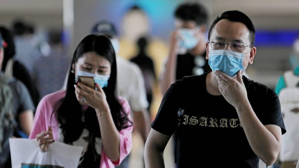 Ciudadados chinos con mascarillas para evitar el contagio del...