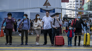 Varias personas usan mascarilla en un paso de peatones de Hong Kong,...