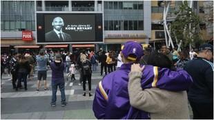 Aficionados se abrazan ante la imagen de Kobe Bryant