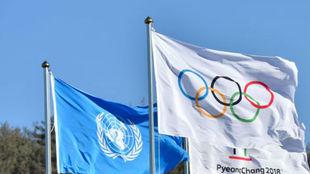 La bandera de la ONU, junto a la bandera olímpica