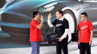 Elon Musk, presidente de Tesla, choca la mano con dos clientes chinos...