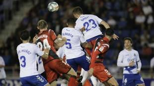 Los jugadores del Tenerife y Rayo saltan a por un balón aéreo