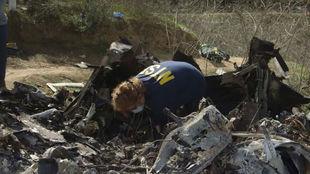 Un agente busca pruebas en el lugar del accidente.