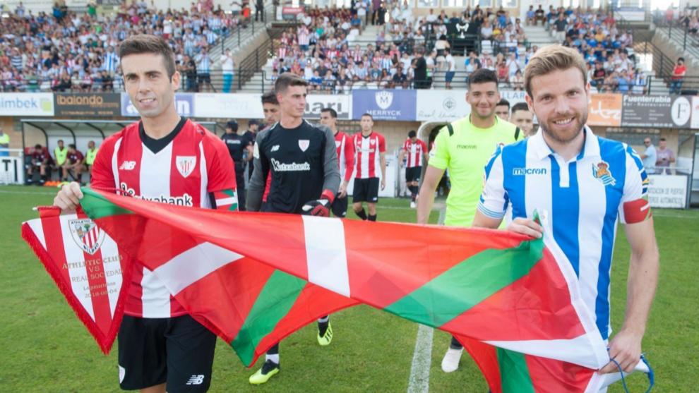 Los jugadores del Athletic y la Real Sociedad salen al campo con la...