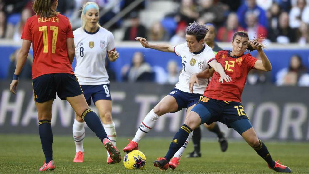 Rapinoe puja un balón con varias jugadoras españolas.