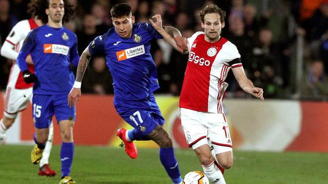 Mathías Olivera  disputa el balón ante el defensa holandés del...
