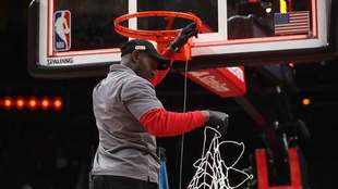 Miembro del staff de la NBA retira la red de la canasta