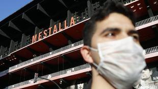 Un aficionado se protege con una máscara delante de la fachada de...