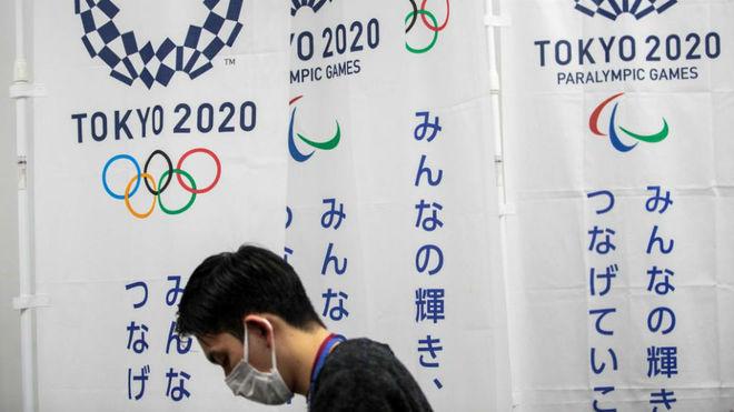 Una persona con mascarilla pasa delante de un cartel de los Juegos de...
